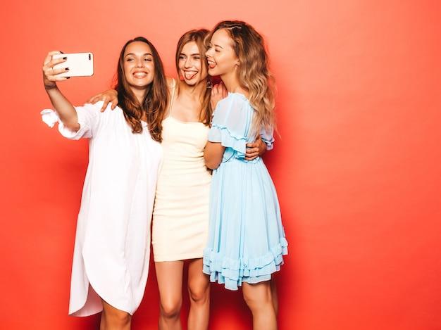 Trois jeunes belles filles hipster souriantes dans des vêtements d'été à la mode. femmes insouciantes sexy posant près du mur rose. des modèles positifs deviennent fous.prenez des photos d'autoportrait selfie sur smartphone
