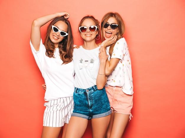 Trois jeunes belles filles hipster souriantes dans des vêtements d'été à la mode. femmes insouciantes sexy posant près du mur rose. les modèles positifs deviennent fous et s'amusent avec des lunettes de soleil