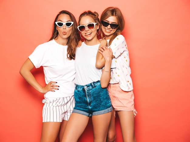 Trois jeunes belles filles hipster souriantes dans des vêtements d'été à la mode. femmes insouciantes sexy posant près du mur rose. des modèles positifs qui deviennent fous et qui s'amusent