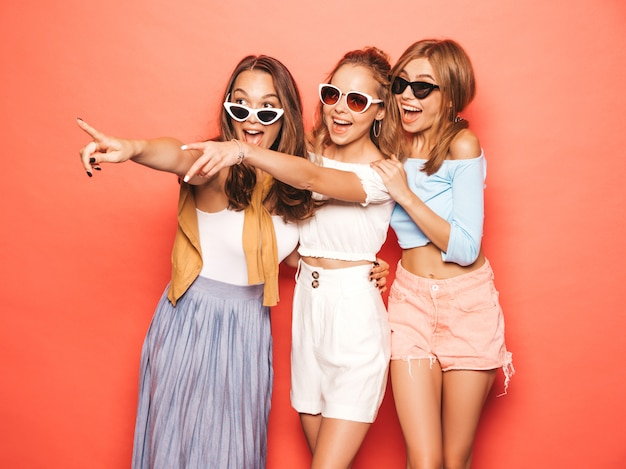 Trois jeunes belles filles hipster souriantes dans des vêtements d'été à la mode. femmes insouciantes sexy posant près du mur rose. des modèles positifs qui s'amusent.