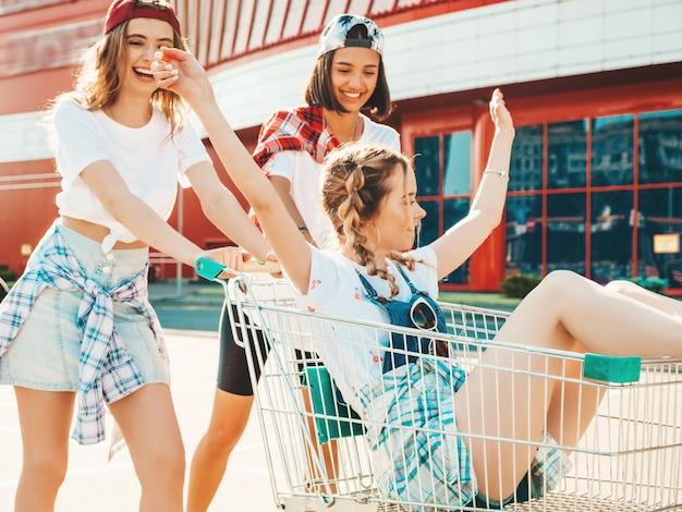 Trois jeunes belles filles s'amusant dans le panier d'épicerie
