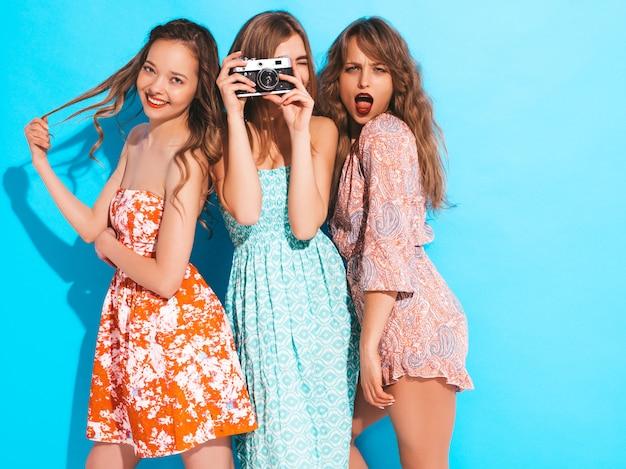 Trois jeunes belles filles souriantes dans des robes colorées d'été à la mode. femmes insouciantes sexy posant. prendre des photos sur un appareil photo rétro