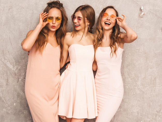 Trois jeunes belles filles souriantes dans des robes rose pâle d'été à la mode. femmes insouciantes sexy posant. modèles positifs en lunettes de soleil rondes s'amusant