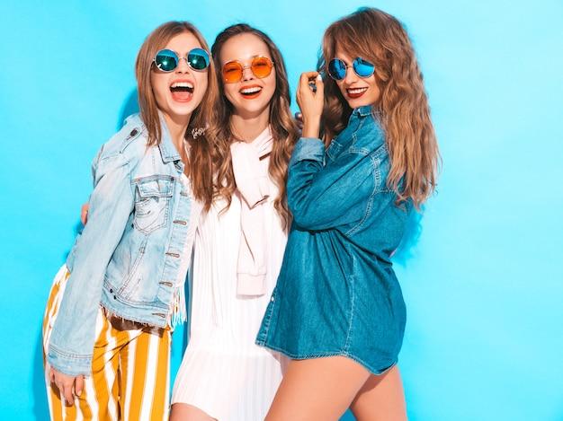 Trois jeunes belles filles souriantes dans des vêtements colorés d'été à la mode. femmes sexy sans soucis en lunettes de soleil isolés sur bleu. modèles positifs