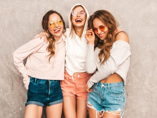 Trois jeunes belles filles souriantes dans des vêtements de sport d'été à la mode. femmes insouciantes sexy posant. modèles positifs en lunettes de soleil rondes s'amusant. étreindre