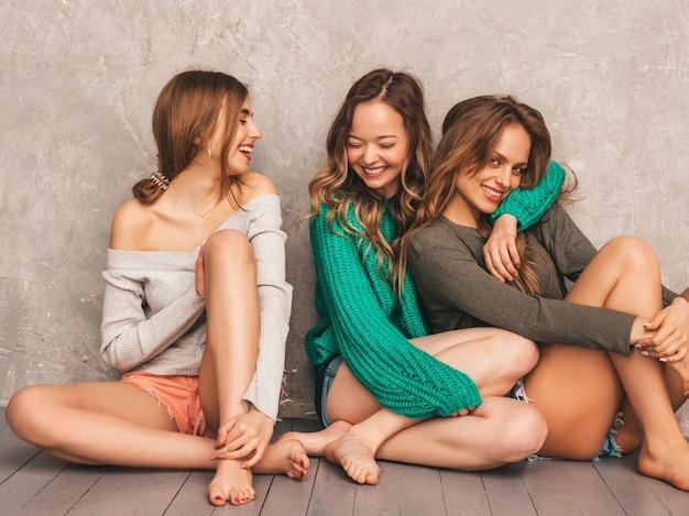 Trois jeunes belles filles souriantes magnifiques dans des vêtements d'été à la mode. femmes insouciantes sexy posant. modèles positifs s'amusant. assis par terre