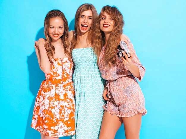 Trois jeunes belles filles souriantes en robes décontractées d'été à la mode. femmes insouciantes sexy posant. prendre des photos sur un appareil photo rétro