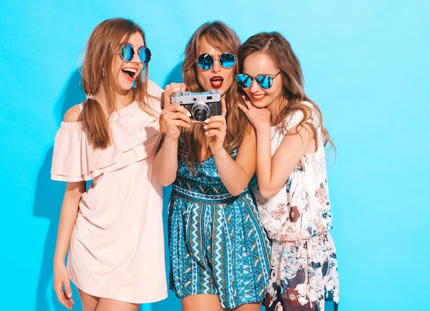 Trois jeunes belles filles souriantes en robes décontractées d'été à la mode et en lunettes de soleil. femmes insouciantes sexy posant. prendre des photos sur un appareil photo rétro
