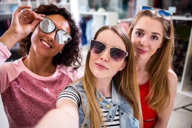 Trois jeunes copines élégantes soulevant des lunettes de soleil à la mode tout en prenant selfie