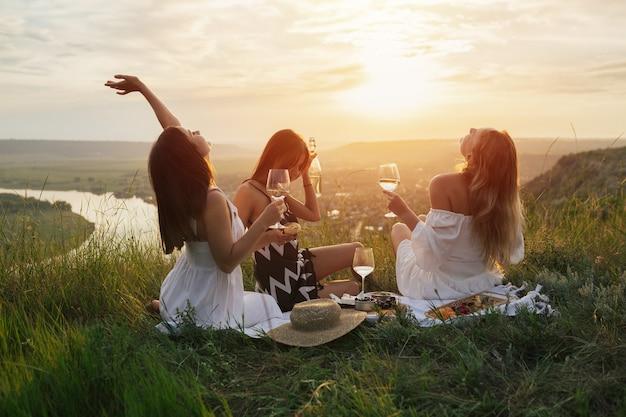 Trois jeunes copines heureuses en robes élégantes pique-nique sur la colline au coucher du soleil.