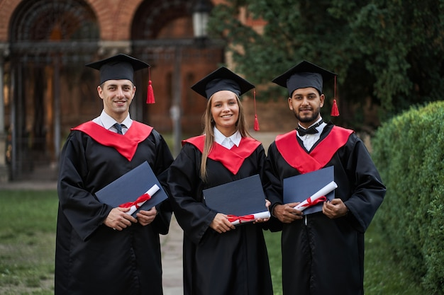 Trois jeunes diplômés heureux de différents pays avec des diplômes en main et en robes de graduation