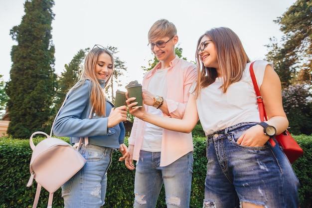 Trois jeunes étudiants, deux belles filles et un beau mec se tiennent debout et boivent du café sur le campus.