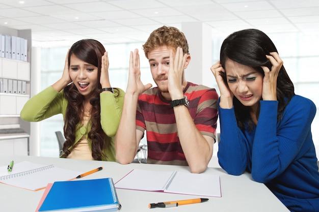Trois jeunes étudiants de stress assis ensemble, isolés