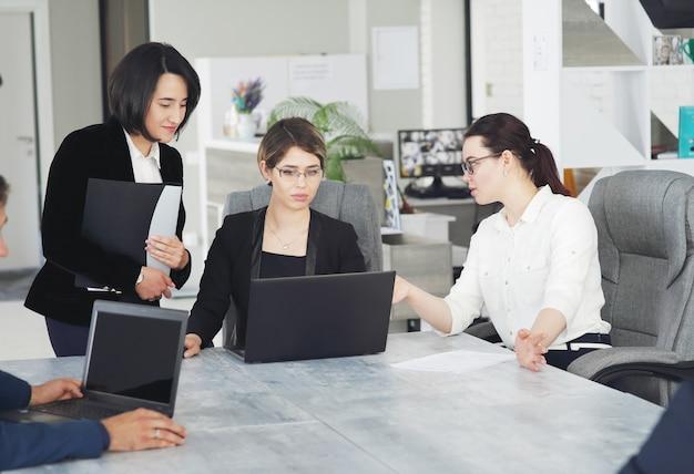 Trois jeunes femmes d'affaires prospères au bureau travaillant ensemble sur un projet