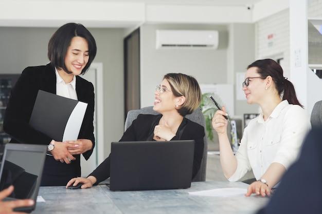Trois jeunes femmes d'affaires prospères au bureau travaillent ensemble avec bonheur sur un projet