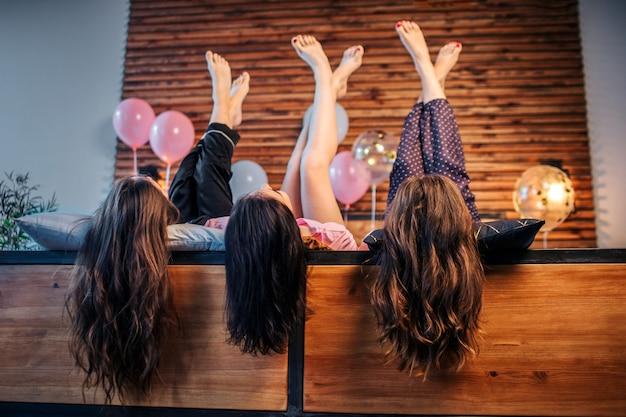 Trois jeunes femmes aux cheveux magnifiques et adorables, allongé sur le lit dans la chambre. ils gardent les jambes levées. les femmes posent.