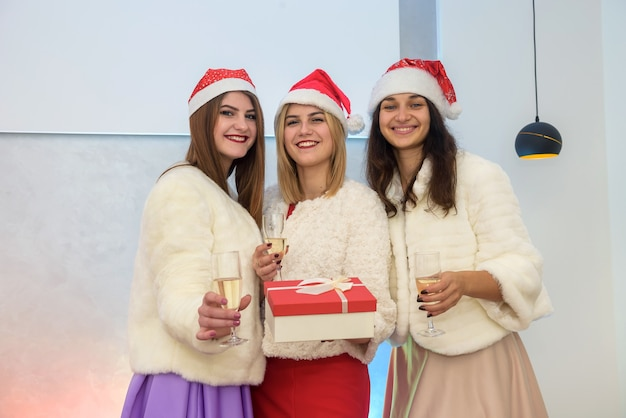 Trois jeunes femmes en chapeaux de père noël avec boîte-cadeau et verres à champagne