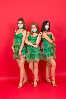 Trois jeunes femmes en costume d'arbre de noël sexy sur fond rouge en studio avec masque de protection