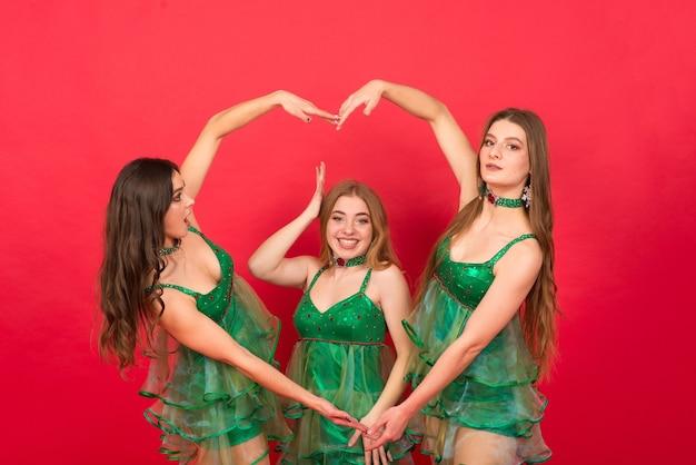 Trois jeunes femmes en costume d'arbre de noël sexy sur fond rouge, studio