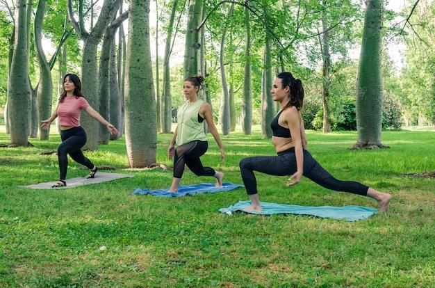 Trois jeunes femmes faisant du yoga dans le parc