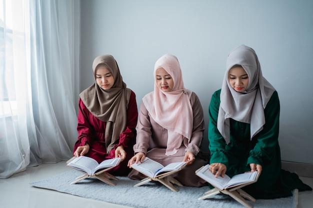 Trois jeunes femmes portant des hijabs lisent ensemble le livre sacré d'al-quran