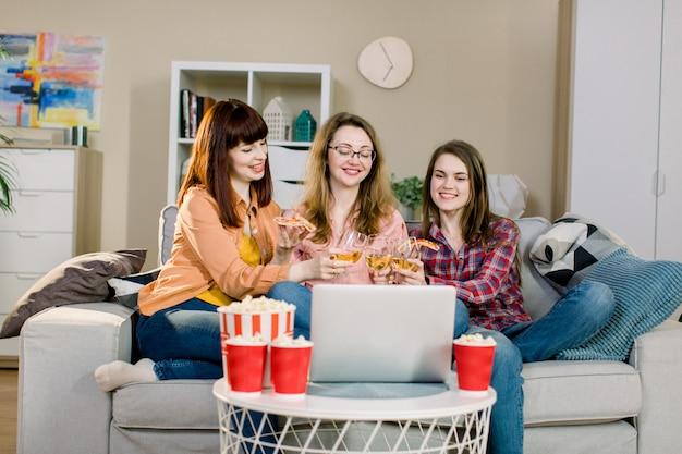 Trois jeunes femmes regardant un film sur un ordinateur portable, riant, buvant du vin et mangeant de délicieux pop-corn à la maison