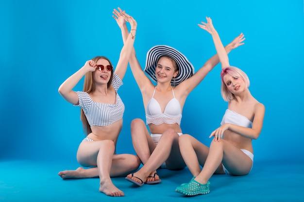 Trois jeunes femmes s'amusant avec les mains en lingerie de maillot de bain isolé sur bleu