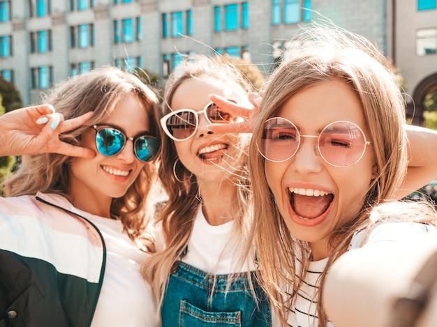 Trois jeunes femmes souriantes hipster dans des vêtements d'été.filles prenant des photos d'autoportrait selfie sur smartphone.modèles posant dans la rue.femme montrant des émotions positives