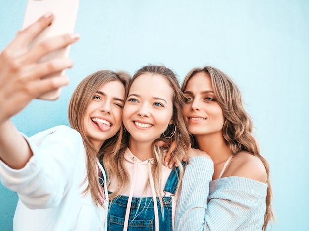 Trois jeunes femmes souriantes hipster en vêtements d'été.filles prenant des photos d'autoportrait selfie sur smartphone.modèles posant dans la rue près du mur.femme montrant des émotions positives