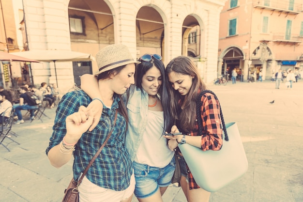 Trois jeunes femmes avec un téléphone intelligent dans la ville