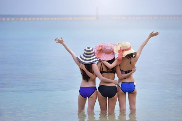 Trois jeunes filles amis se détendre sur la plage