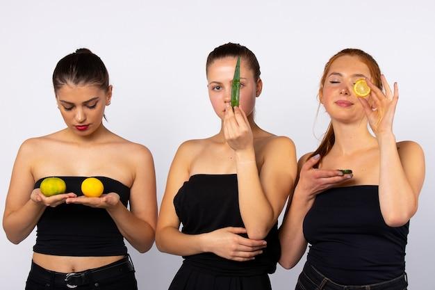 Trois jeunes filles attrayantes avec des fruits et une feuille d'aloès. isolé sur blanc. peau saine et concept de nourriture saine. photo de haute qualité