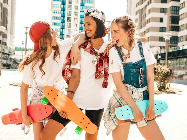 Trois jeunes filles belles souriantes avec des planches à roulettes penny colorées.