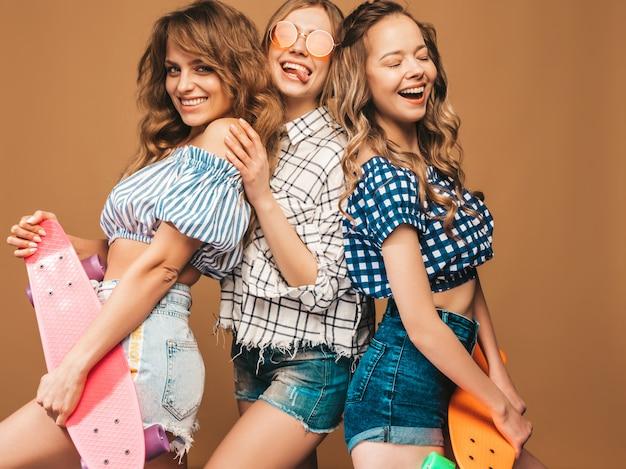 Trois jeunes filles élégantes souriantes sexy sexy avec des planches à roulettes penny colorés. femmes en vêtements de chemise à carreaux d'été posant dans des lunettes de soleil. modèles positifs s'amusant