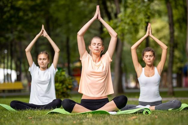 Trois jeunes filles faisant du yoga assis sur des tapis de yoga sur l'herbe verte dans le parc par une chaude journée.