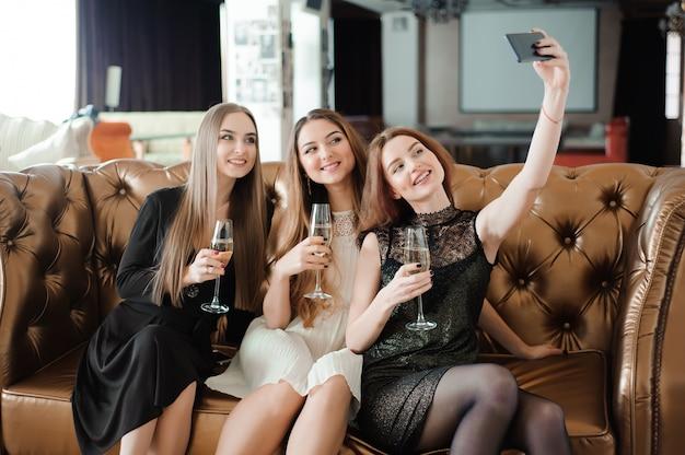 Trois jeunes filles font une photo de selfie dans un restaurant.