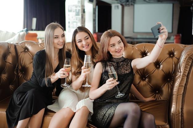 Trois jeunes filles font une photo selfie dans un restaurant.