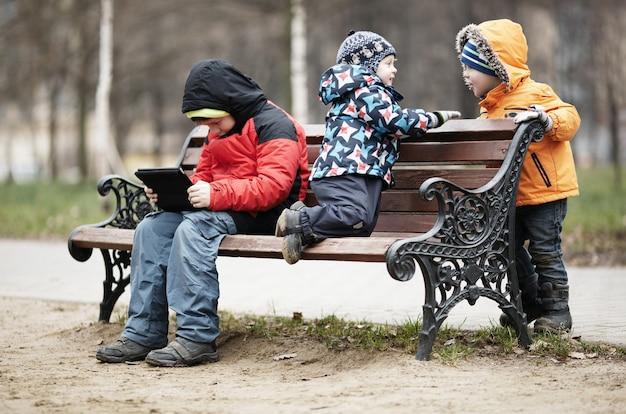 Trois jeunes garçons jouant sur un banc de parc en hiver