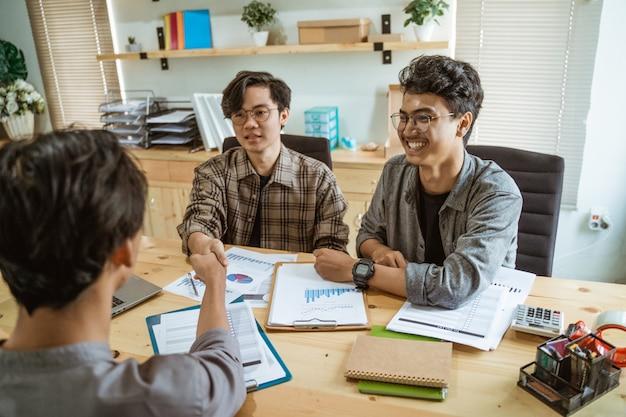 Trois jeunes gens d'affaires asiatiques se sont serré la main en accord