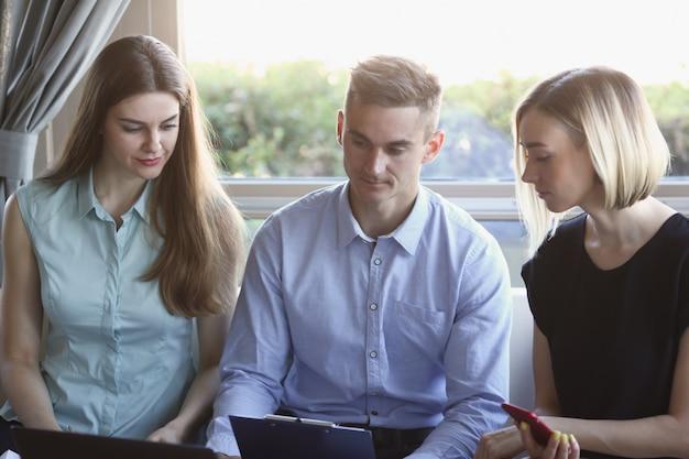 Trois jeunes gens d'affaires dans un café discutant du problème du travail d'équipe
