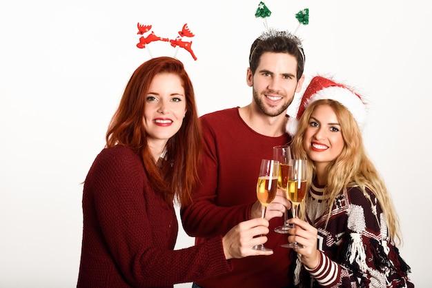 Trois jeunes gens, grillage, champagne sur fond blanc
