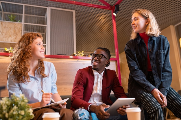 Trois jeunes gestionnaires joyeux discutant des questions de travail lors d'une réunion dans un café ou un bureau contemporain