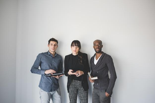 Trois jeunes hommes d'affaires multiethniques posant à la recherche d'appareil photo