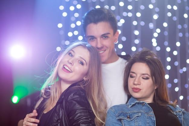 Trois jeunes hommes et deux femmes s'amusent dans une boîte de nuit lors d'une fête