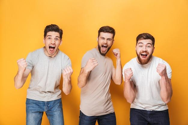 Trois jeunes hommes excités célébrant le succès ensemble