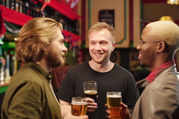 Trois jeunes hommes interculturels joyeux se regardent tout en trinquant avec des verres de bière devant la caméra dans un environnement de pub