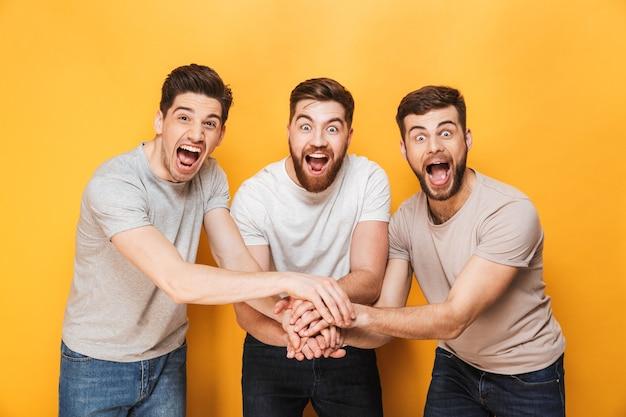 Trois jeunes hommes joyeux célébrant ensemble le succès