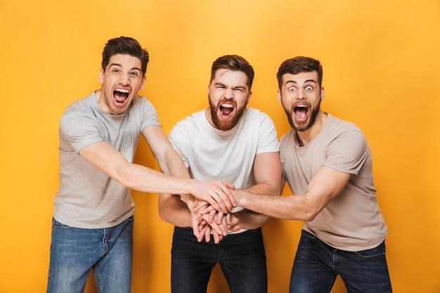 Trois jeunes hommes joyeux célébrant le succès ensemble
