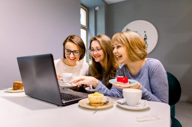 Trois jeunes jolies femmes utilisent un ordinateur portable au café