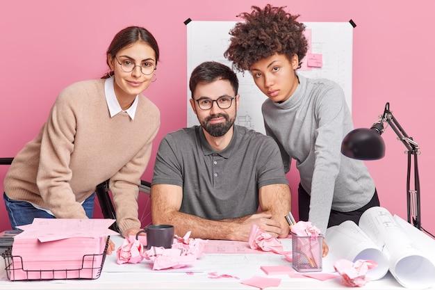 Trois jeunes personnes motivées discutent d'un plan de coopération sur des poses de projets architecturaux communs dans un bureau de coworking moderne collaborent pour faire de la recherche